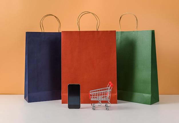 Papieren boodschappentassen en winkelwagentje of trolley met telefoon op witte tafel en pastel