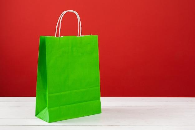 Papieren boodschappentassen met kopie ruimte op rood