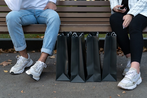 Papieren boodschappentassen naast shoppers die op de bank rusten. voeten van jonge man en vrouw na het winkelen.