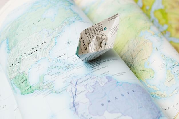 Papieren boot bovenop kaarten
