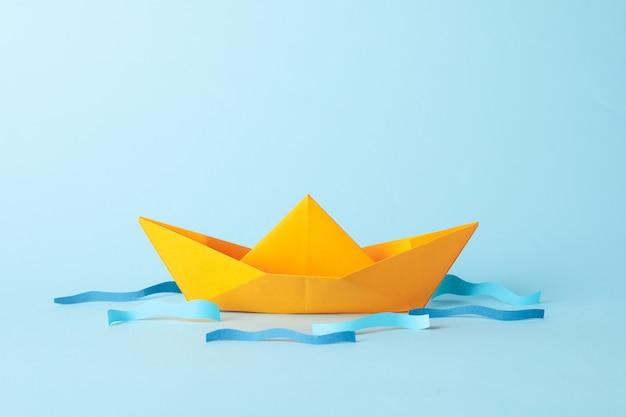 Papieren boot en golven op blauw, ruimte voor tekst