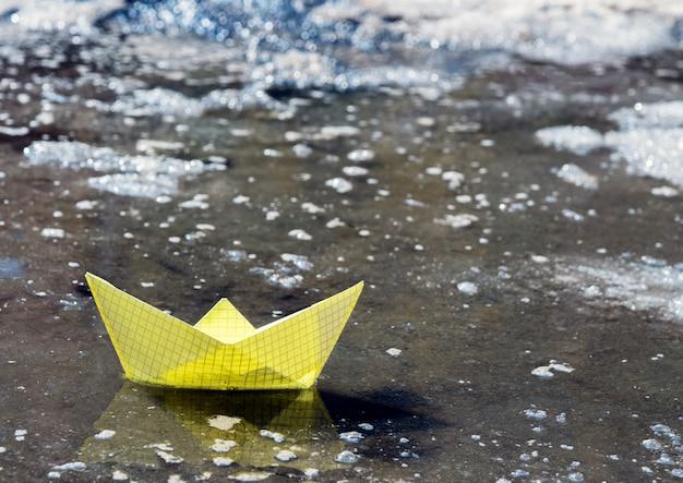 Papieren boot in een voorjaar plas water tussen het ijs