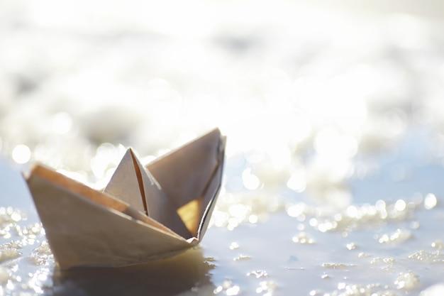 Papieren boot in het water op straat. het concept van de vroege lente. smeltende sneeuw en een origamiboot op watergolven.