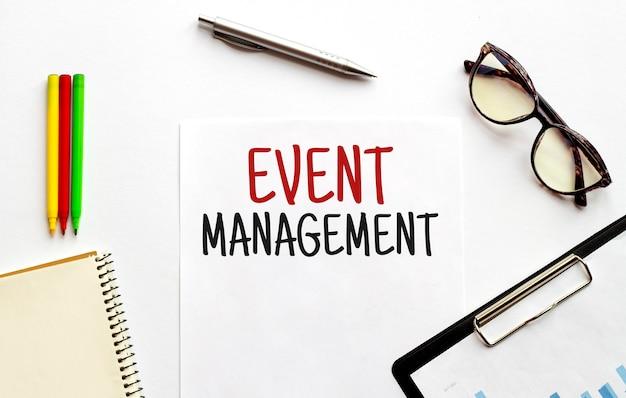Papieren bord glazen blocnote en potloden op de witte achtergrond bedrijfs concept tekst event management
