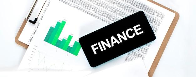 Papieren bord met financiële bedragen, groen diagram en telefoon op het witte bureau. bedrijfsconcept.