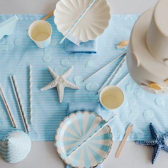 Papieren borden op voorbereide verjaardagstafel met voor kinderen of meisjesfeest in hemelsblauwe en witte kleuren. zee stijl. baby jongen douche. bovenaanzicht