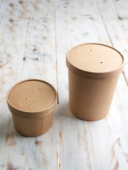 Papieren containers voor afhaalmaaltijden voor drankjes of soep, geïsoleerd op houten