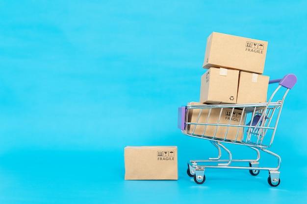 Papieren dozen in een trolley op blauwe achtergrond. online winkelen of ecommmerce concept en levering dienstverleningsconcept met kopie ruimte