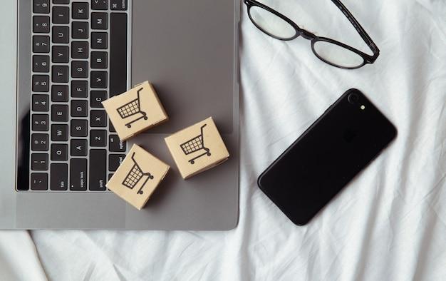 Papieren dozen of pakket op een laptop toetsenbord in de buurt van smartphone. boodschappenservice op internet en bezorging aan huis.