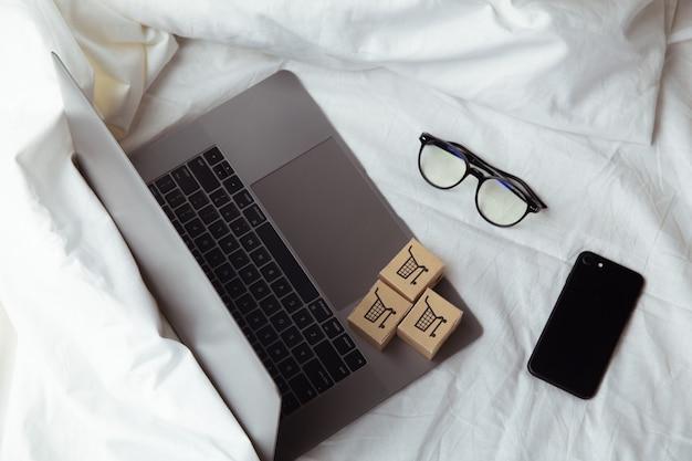 Papieren dozen of pakket op het toetsenbord van een laptop in de slaapkamer. boodschappenservice op het online web en bezorging aan huis.