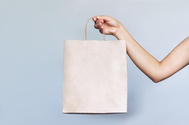 Papieren eco-vriendelijke tas met lege ruimte voor het logo in een vrouwelijke hand op een grijze achtergrond
