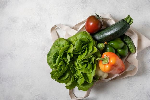 Papieren en katoenen zak met gezonde groenten, plat voedsel op tafel. bovenaanzicht, kopieer ruimte.