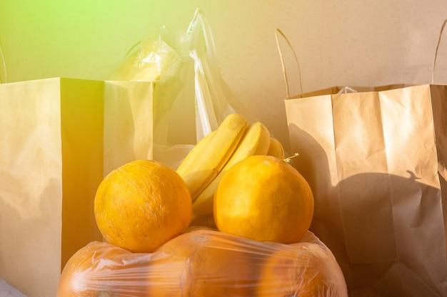 Papieren en plastic zakken pakketten met eten op tafel