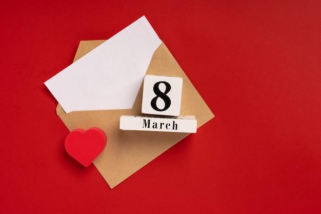 Papieren envelop voor groeten en een wit vel met ruimte voor tekst op internationale vrouwendag