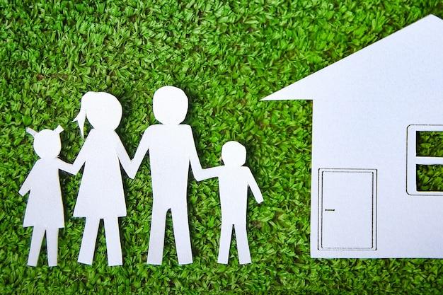 Papieren familie met een huis op een achtergrond van gras
