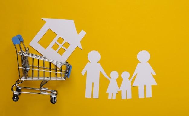 Papieren familie samen en winkelwagentje met huis op een geel. huis kopen concept