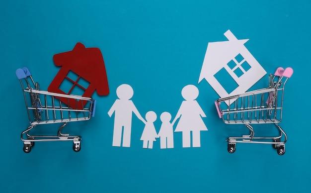 Papieren familie samen en winkelwagentjes met huis op blauw. huis kopen concept