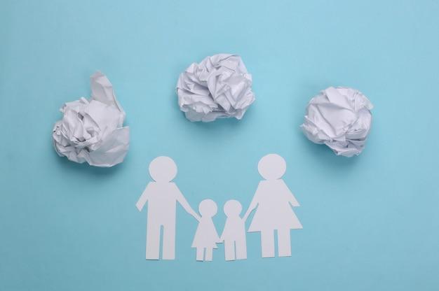 Papieren familieketting met verfrommelde papieren ballen op een blauw. familie problemen