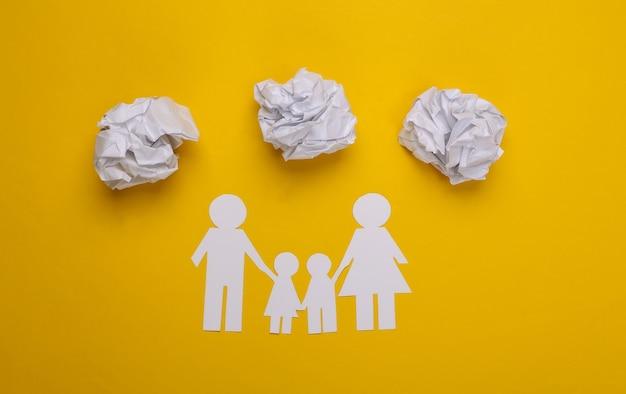 Papieren familieketting met verfrommelde papieren ballen op geel. familie problemen