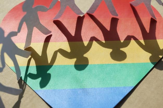 Papieren figuren hand in hand op de achtergrond van het hart van de seksuele minderheid van het lgbt-symbool