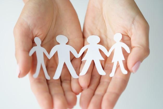 Papieren figuren van familie worden in handpalmen gehouden, liefde en relatieconcept