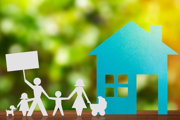 Papieren figuur van een paar hand in hand met kinderen. blue house en onscherpe achtergrond.