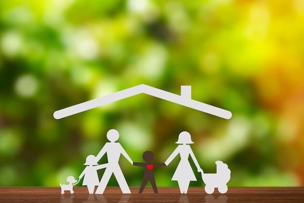 Papieren figuur van een paar hand in hand met kinderen en een pleegzoon. blauw huis en onscherpe achtergrond. diversiteit, concept van minderheden.