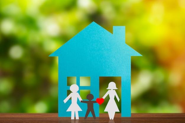 Papieren figuur van een vrolijk paar hand in hand met pleegkind. blauw huis en aangeduide achtergrond. diversiteit, concept van minderheden.