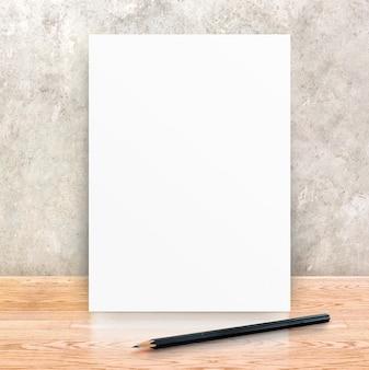 Papieren fotolijst en zwart potlood op betonnen muur en houten plankenvloer, bespotten voor het toevoegen van uw inhoud,
