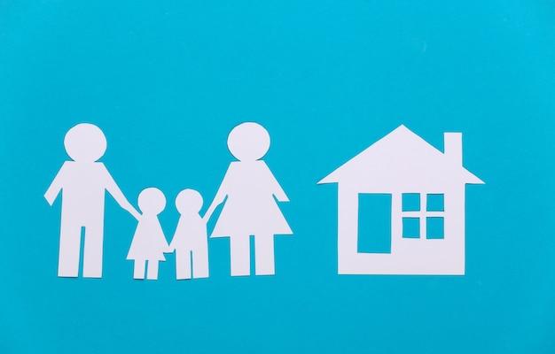 Papieren gelukkige familie met huis op blauw