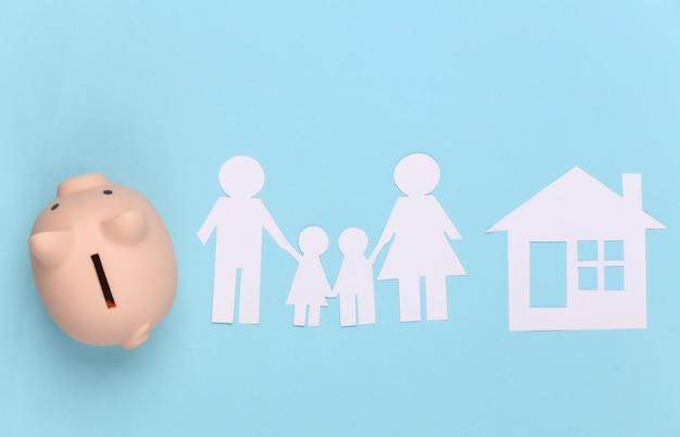 Papieren gelukkige familie samen met huis en spaarvarken op blauw. gezinsbudget