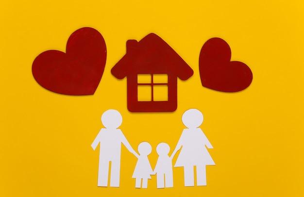 Papieren gelukkige familie samen met huis, rode harten op geel