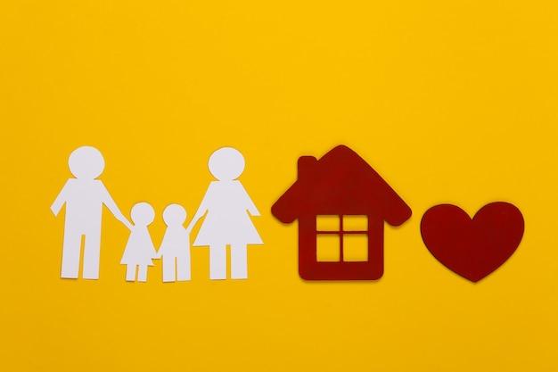 Papieren gelukkige familie samen met huis, rood hart op geel