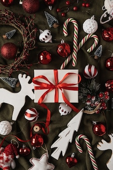 Papieren geschenkdoos met vlinderdas en kerstballen, zuurstokken, speelgoed op groene verfrommelde deken. bovenaanzicht, plat gelegd.