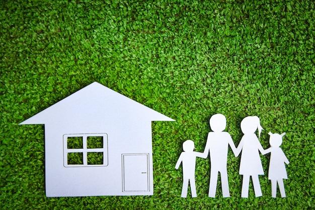 Papieren gezin met een huis op een gras