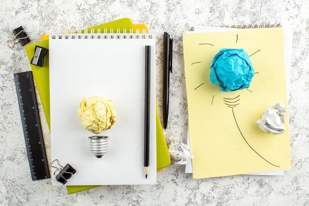Papieren gloeilamp op wit gesloten spiraalvormig notitieboekje en kantoorbenodigdheden op wit oppervlak