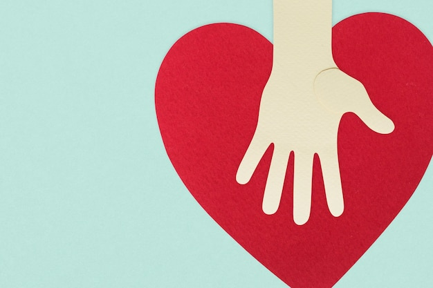 Papieren hand met een hart dat donaties ondersteunt tijdens een pandemische achtergrond van het coronavirus
