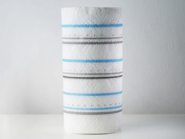 Papieren handdoeken rollen met blauwe strepen op een witte tafel.