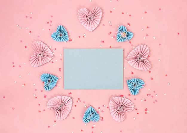 Papieren harten in scrapbookingtechniek en roze en rode snoepjes suiker snoep harten vliegen uit op de living coral-achtergrond. valentijnsdag. liefde concept. ruimte voor tekst. brede banner - afbeelding.