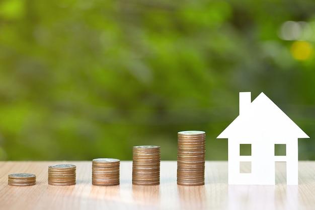 Papieren huis op stapel munten om te sparen om een huis te kopen.