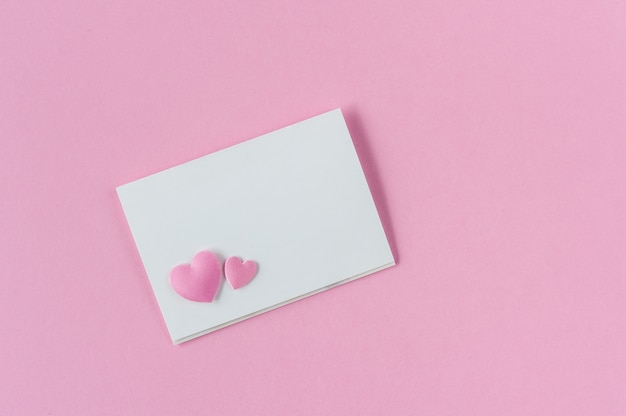 Papieren kaart op roze met twee harten.