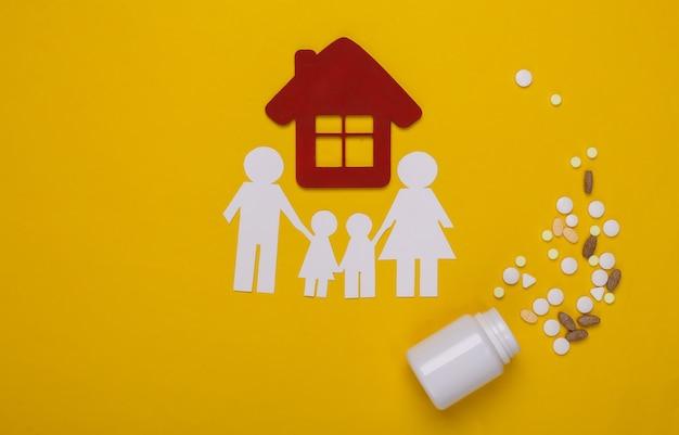 Papieren ketting familie, huis en fles pillen op geel, ziektekostenverzekering concept