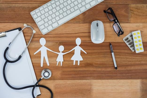 Papieren ketting uitgesneden met medicijn, muis, toetsenbord, stethoscoop, klembord en bril