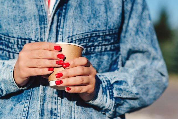 Papieren koffiekopje in handen van de vrouw met perfecte manicure. vrouwelijke hand met koffie om mee te nemen. vrouw met kopje in handen. afhaalkoffie drinken.