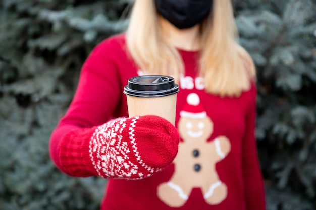 Papieren koffiekopje in handen van vrouwen. onscherpe achtergrond