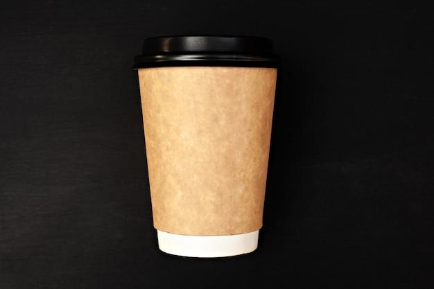 Papieren koffiekopje op zwarte achtergrond