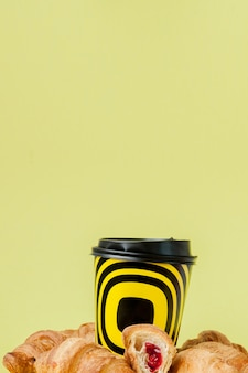 Papieren kopje koffie en croissants op een geel