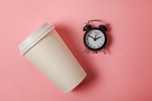 Papieren kopje koffie en wekker op roze achtergrond