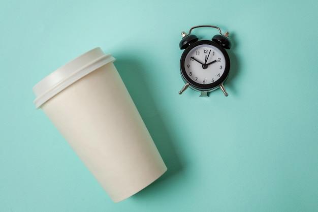 Papieren kopje koffie en wekker