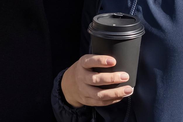 Papieren kopje koffie in de hand. zwarte papieren kopje koffie in de hand.
